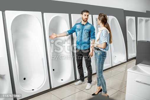 istock Couple choosing new bathtub in the shop 1137575892