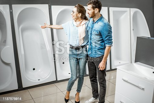 istock Couple choosing new bathtub in the shop 1137575914
