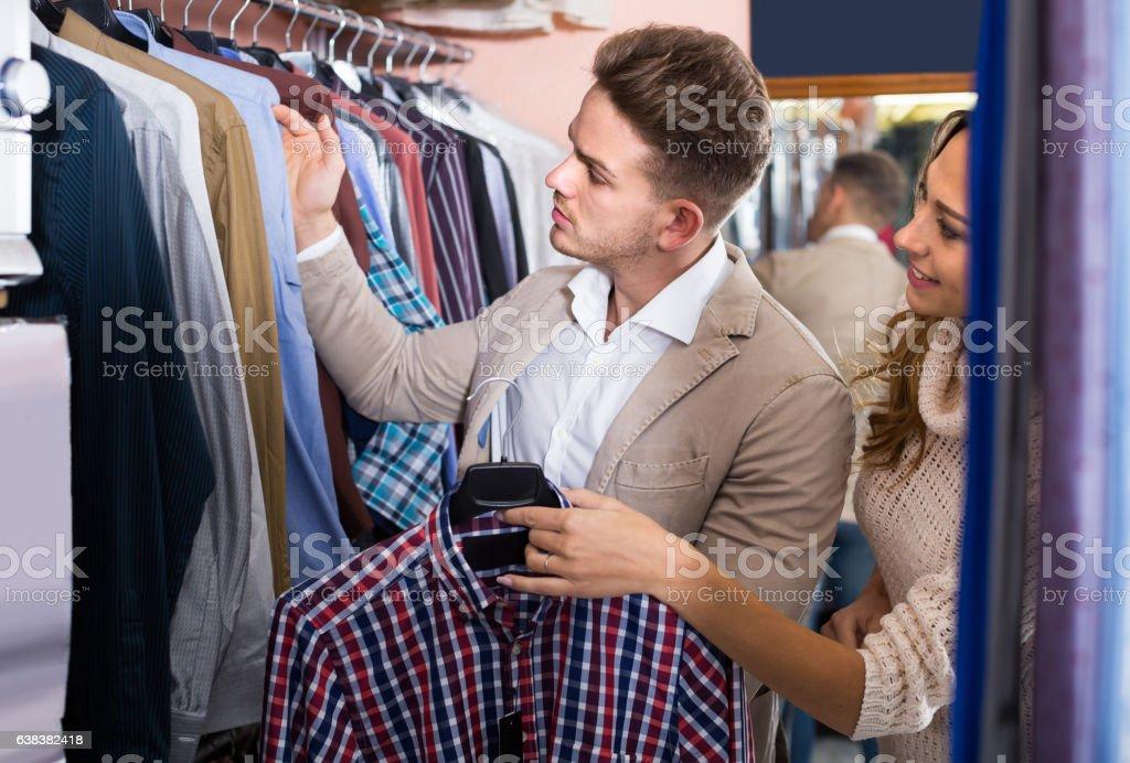 couple choosing new shirt in men's cloths store stock photo