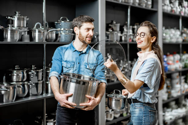couple choosing pans for cooking in the shop - happy person buy appliances stock photos and pictures