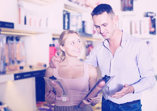 Couple choosing sex toy in sex shop stock photo