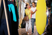 Young positive couple choosing surfboard in sporting goods store