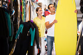 Young couple choosing surfboard in sporting goods store