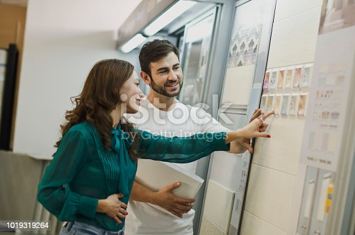 Couple choosing tiles in ceramic and furniture shop for their house