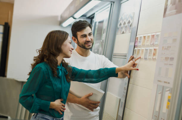 Couple choosing tiles in ceramic and furniture shop for new home - foto stock