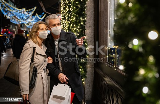 Happy couple Christmas shopping during the pandemic wearing a facemask and looking at a shop window while carrying bags