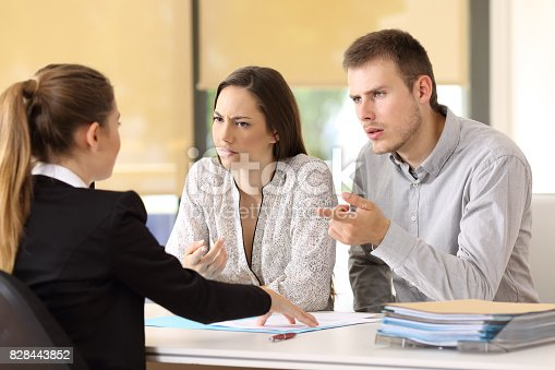 istock Couple claiming to a businesswoman at office 828443852