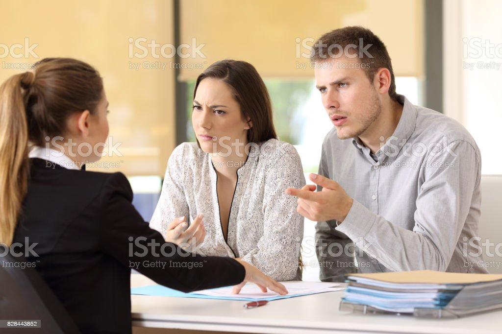 Couple claiming to a businesswoman at office stock photo