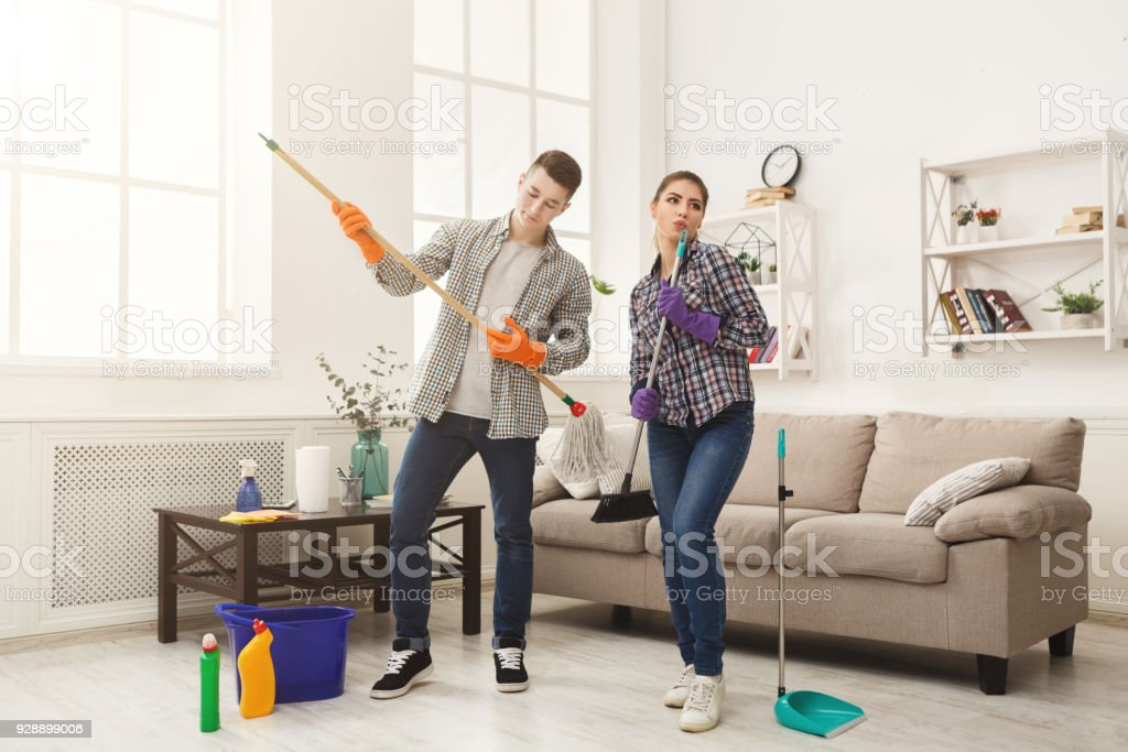 Couple cleaning at home together stock photo