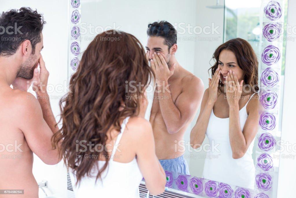 Couple de nettoyage visage tout en regardant dans le miroir photo libre de droits
