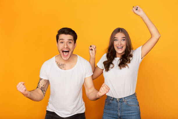 Couple clenching fists like winners over yellow background stock photo