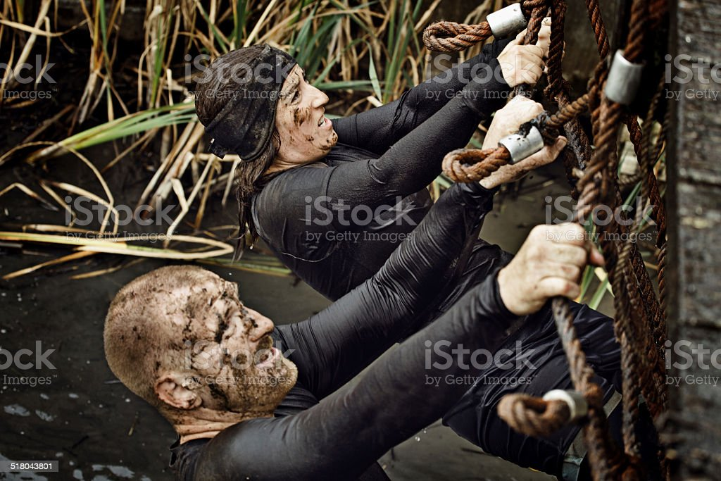 couple climbing on net during obstacle run in Holland stock photo