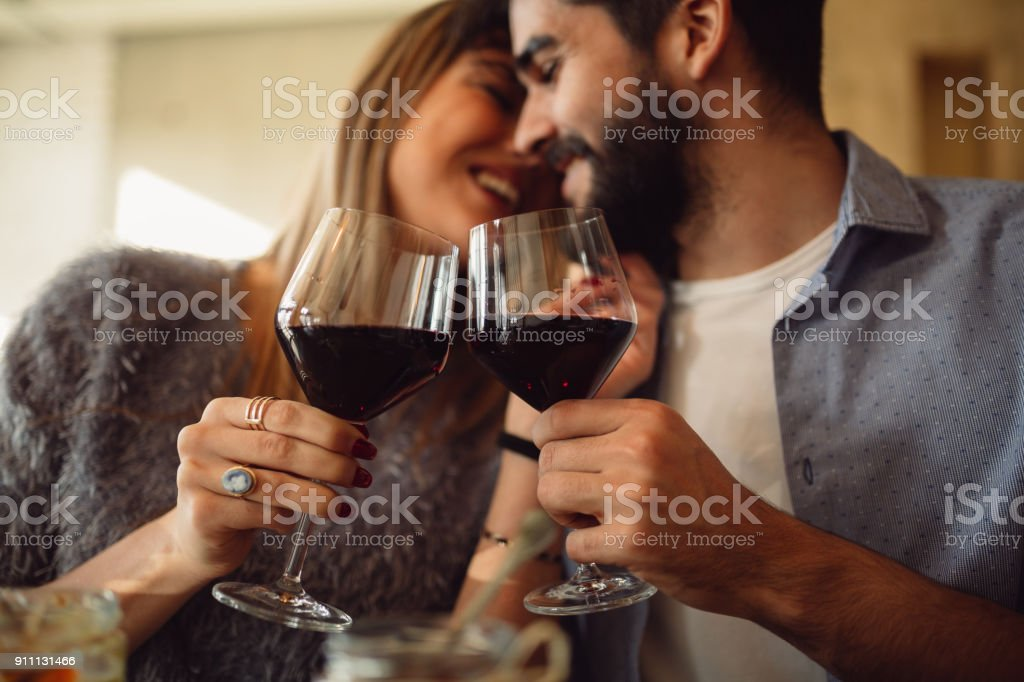 Couple clink glasses with red wine at date in casual outfit in cafe. Couple having romantic moments. stock photo