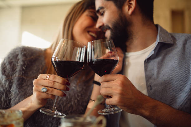 couple clink glasses with red wine at date in casual outfit in cafe. couple having romantic moments. - couple lap stock photos and pictures