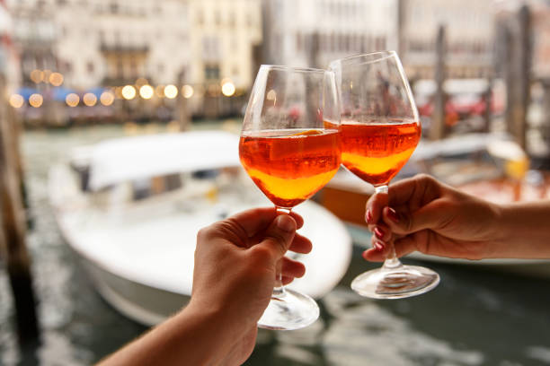 Couple clinking glasses with Spritz in Venice, Italy stock photo