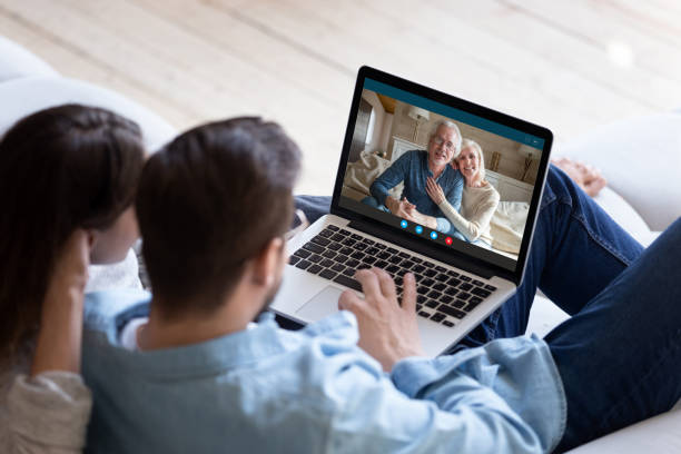 Couple communicating with elderly parents using laptop and videocall app stock photo