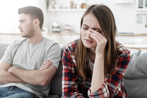 couple conflict. stressed crying female sitting on couch with abusive husband after quarrel, ready to divorce - relationship difficulties stock pictures, royalty-free photos & images