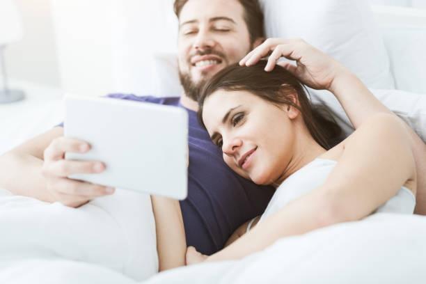 Couple connecting with a tablet stock photo