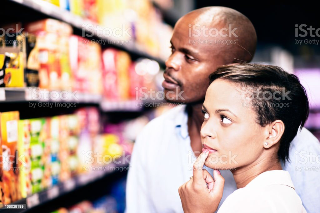 Couple considering products on shelves in supermarket royalty-free stock photo