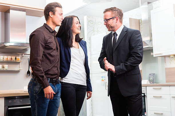 Couple consult salesman for domestic kitchen Man and woman consult salesman for domestic kitchen in studio or furniture store showroom stock pictures, royalty-free photos & images