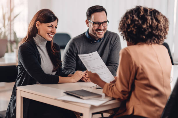 Couple consulting with a female financial manager at the bank stock photo