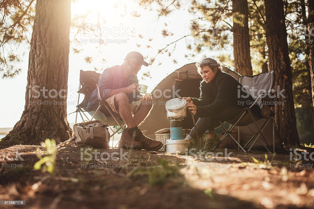 Couple cooking food outdoors on a camping trip stock photo