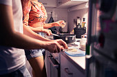 Couple cooking in home kitchen. Two people preparing a meal and dinner together. Husband and wife romantic date night. Happy friends or family making a healthy dish. Woman seasoning food with spice.