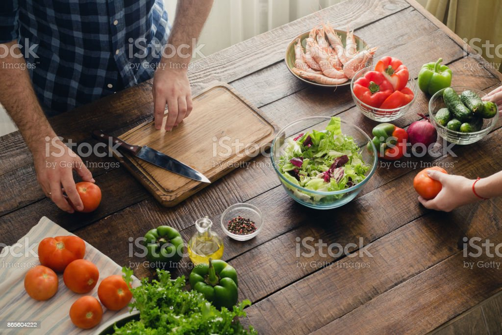 Couple cooking together dinner salad of vegetables and shrimp salad on wooden table in home kitchen stock photo