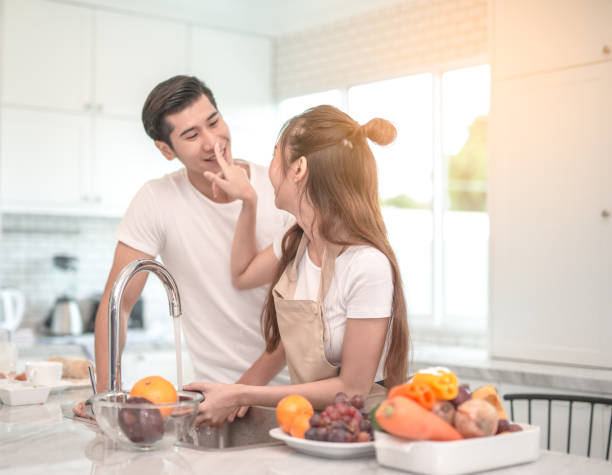 couple cooking together in the kitchen at home. stock photo