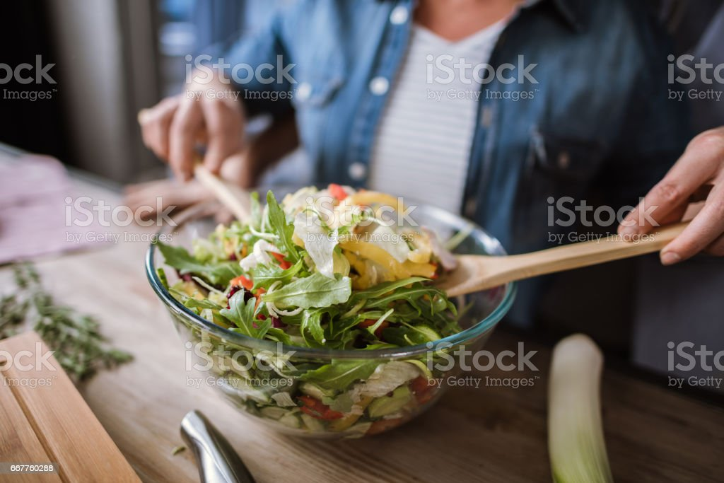 Couple cooking vegetable salad stock photo