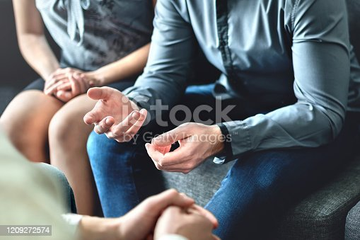Couple counseling or therapy session. Man talking about problems in the family. Husband and wife meeting their psychiatrist. Discussion with marriage counselor, mediator or relationship psychologist.