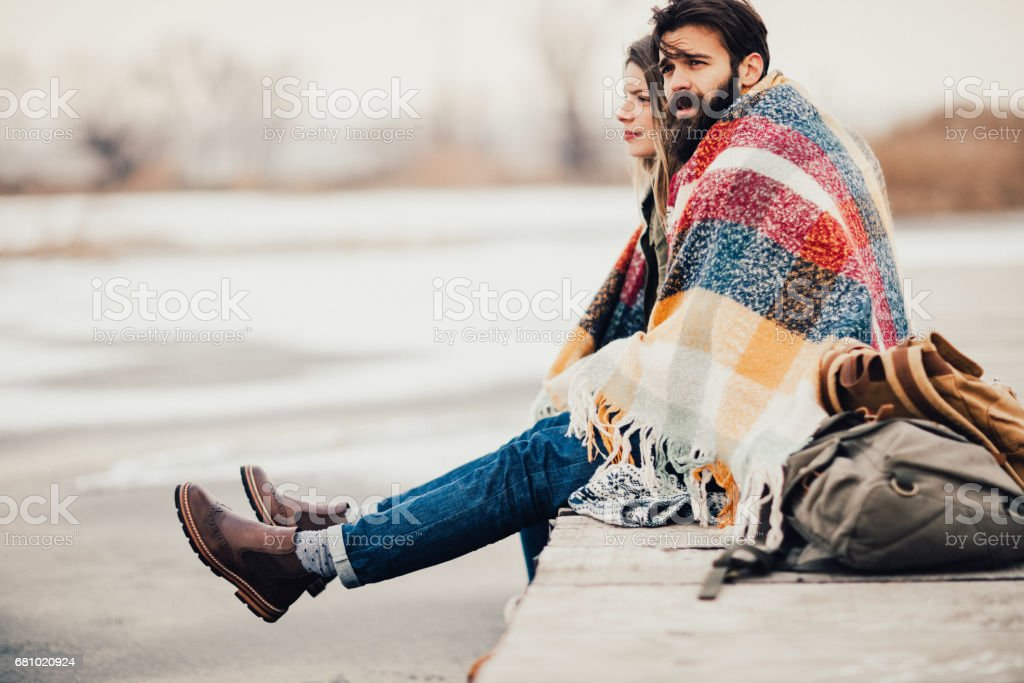Couple covered with blanket on a cold day in november.