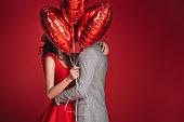 赤に分離された風船の束で顔を覆ってカップル