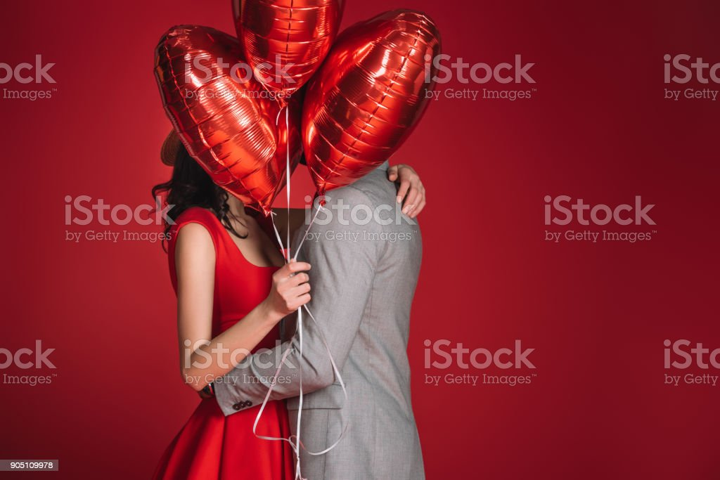 couple covering faces with bundle of balloons isolated on red stock photo
