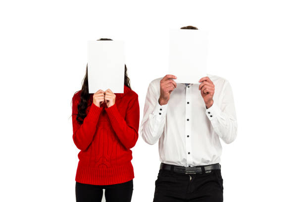 Couple covering their faces with documents stock photo
