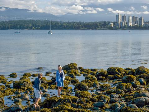 Couple cross tidal rocks, city skyline distant