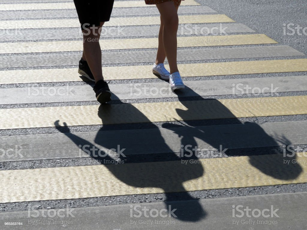 A couple crossing the street at a crosswalk zbiór zdjęć royalty-free