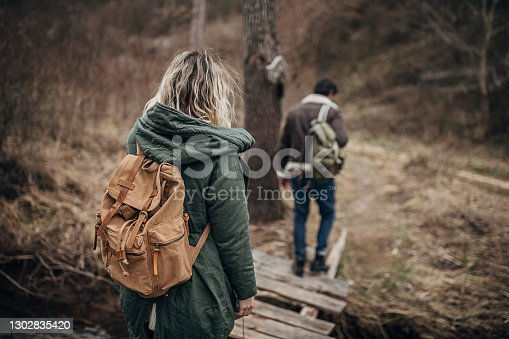 Man and woman, beautiful young couple hiking together, crossing a wooden bridge in nature on a winter day.