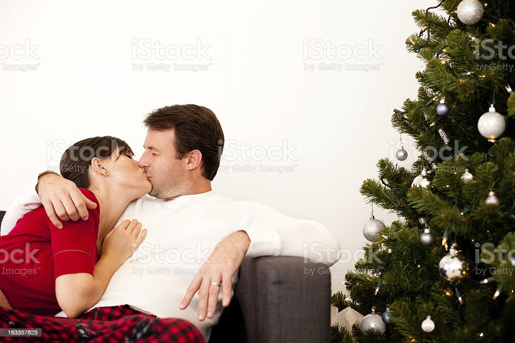 Couple Cudding and Kissing on Couch by Christmas Tree stock photo