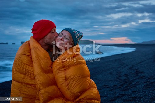 Man and Woman on rocky beach background. Cuddling in a sleeping bag