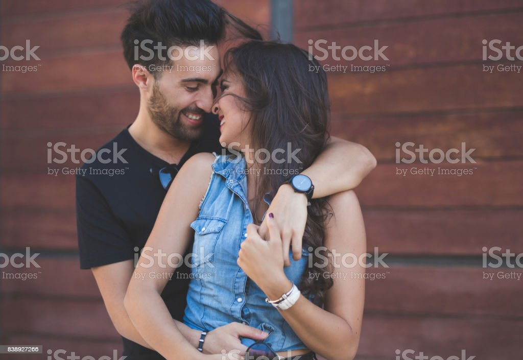 Couple cuddling together touching each other nose laughing stock photo