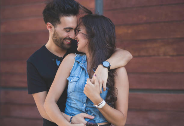 couple cuddling together touching each other nose laughing - love at first sight stock photos and pictures