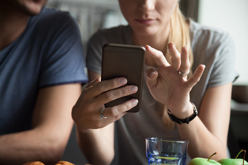 Couple customers holding mobile phone using smartphone apps, close up
