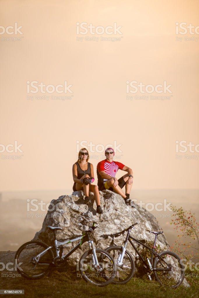 Ciclistas de casal sentado na pedra perto de bicicletas à noite - foto de acervo