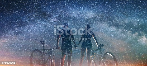 istock Couple cyclists with mountain bikes at night under starry sky 678626966