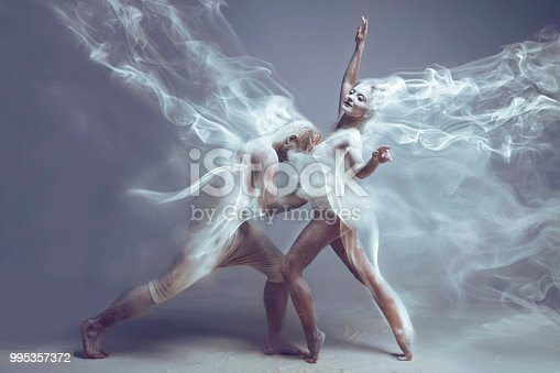 Dancing in flour. Couple in love in dust / fog. Girl and guy dancers wearing white sport clothing dancing in flour cloud on isolated background. Surreal concept.