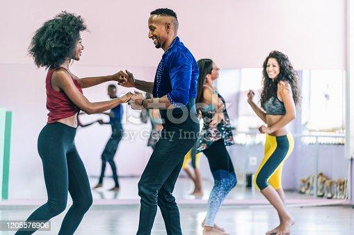 Couple dancers practicing in studio, holding hands