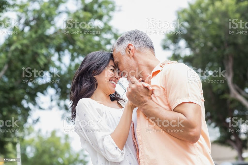 Couple dancing against trees stock photo