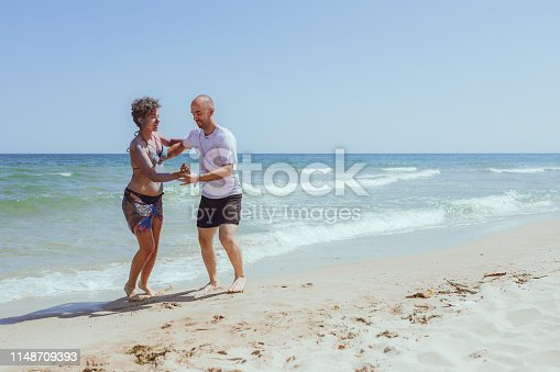 Young, playful couple dancing on the beach of Albena, Bulgaria with sea and clear sky as background.