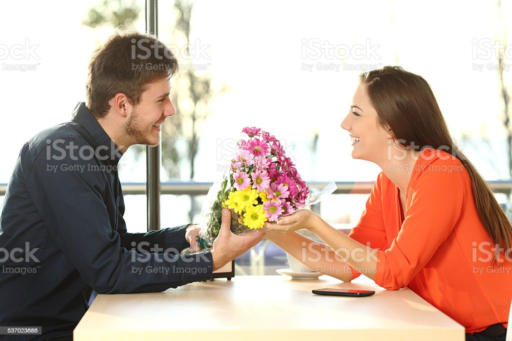 Couple date with man giving flowers stock photo